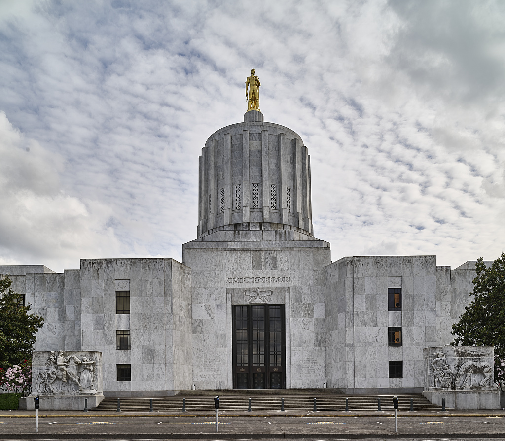 The Oregon State Capitol in Salem, an attractive building built of light and dark gray stone, illustrating a page about collections services in New York State.